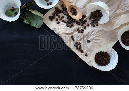 spilled coffee beans on brown paper on a black table with hearts