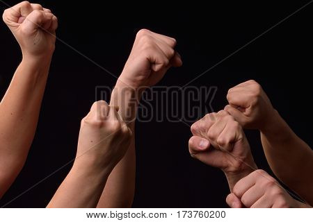 Group Of Female And Male Hands Showing Fists Raised Up On Black Background. Team. Power. Leader. Rev