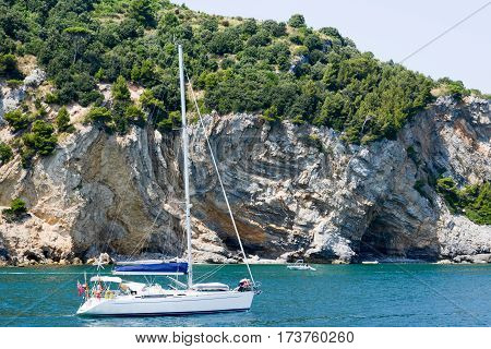 People Sailing With A Sailboat In Front Of Palmaria Island