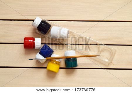 Harmless red, black, green, yellow, white wooden paint in small glass bottle