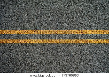 Double yellow lines on the asphalt road in the middle.