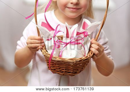 Cute girl holding basket with paper bags in shape of Easter rabbits, closeup