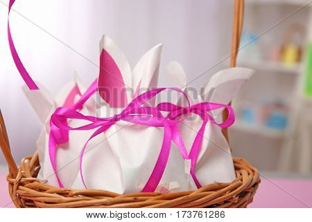 Wicker basket with paper bags in shape of Easter rabbits on blurred background, closeup
