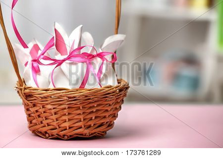 Wicker basket with paper bags in shape of Easter rabbits on table against blurred background