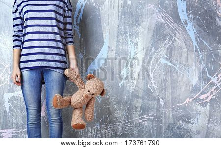 Little girl standing with toy bear on color wall background