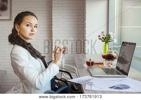Businesswoman leaning back in chair holding in one hand pen and other hand paper. Graphics, open laptop, tea set, vase with roses stand on table, black and white chairs at table, handbag on chair.