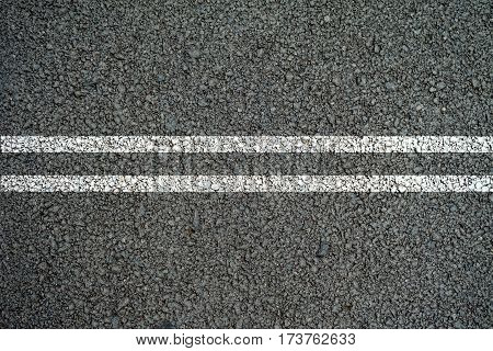 Double white lines on the asphalt road in the middle.