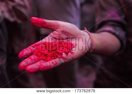 Hand with powdered red dye during for Holi celebration in India. Detail shot