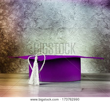 Graduation Mortarboard On Wooden Table On Background Of Vintage Wall