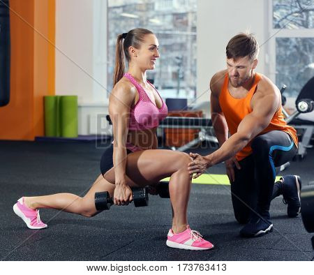 Beautiful sportive woman training with her trainer in gym poster