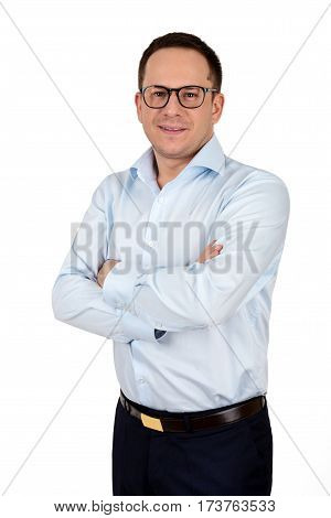 Young businessman in glasses stands with crossed arms against white background