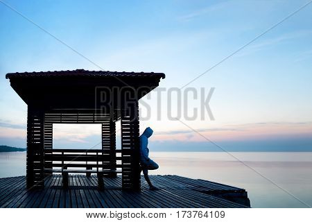 Frustrated depressed man wearing hoodie standing alone on wooden bridge extended into the sea looking down and contemplating suicide. Concept of unemployed sadness depression and human problems.