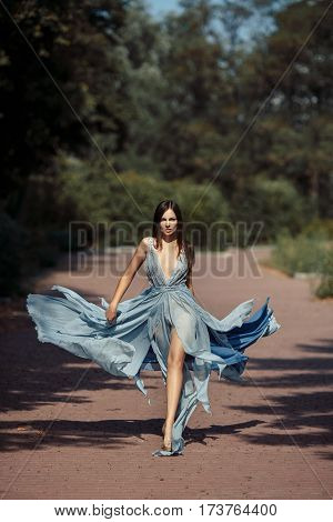Fashion outdoor photo of beautiful sensual woman in long luxury blue dress summer park. Multi-racial Asian Caucasian model walking and posing outdoors. Fashionable toning. Shot of the girl in full length