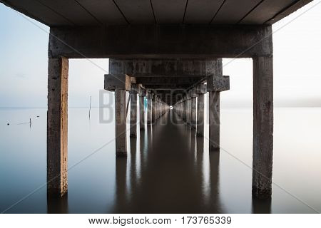 under view of bridge extended into the sea with water reflection. long exposure photography. the concept of lonely sadness depressed and broken heart.