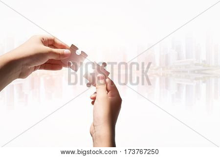 Hands holding jigsaws with the blurred cityscape background concept for business success.