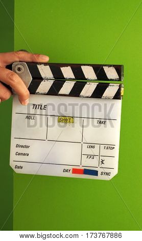 Movie slate board or clapper board and man hand and white color and green screen background in studio.