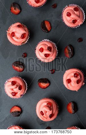Cupcakes With Pink Frosting And Chocolate Covered Strawberry Slices Background