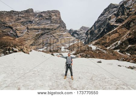 Man with backpack trekking in mountains. Cold weather snow on hills. Winter hiking. Vintage effect style pictures.