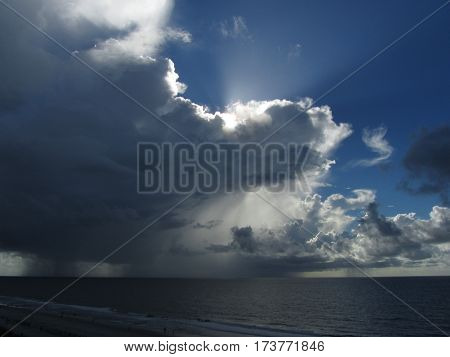 sunlight streaming from behind cumulus clouds and rain squall over the Atlantic ocean