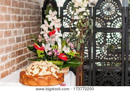Wedding loaf with poppy seeds and flowers on a table. Composition with white orchids