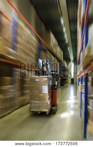 forklift with pallet moving at high speed between the pallet racks in the warehouse