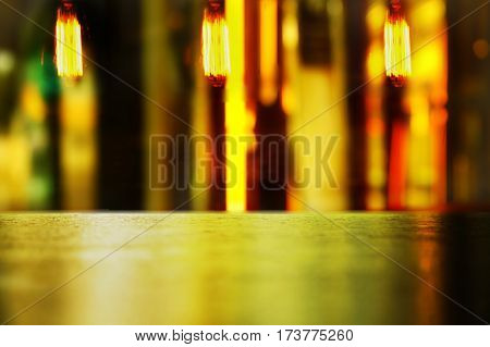 wood table display with vibrant abstract light and bulb lamp in bar in the dark night background