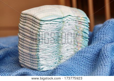 Stack of diapers or nappies on knitted blanket closeup