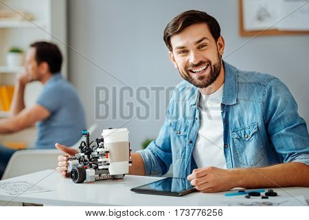 Great job. Cheerfyl professional engineer testing robot and working in a lab while his collegue using laptop in the background