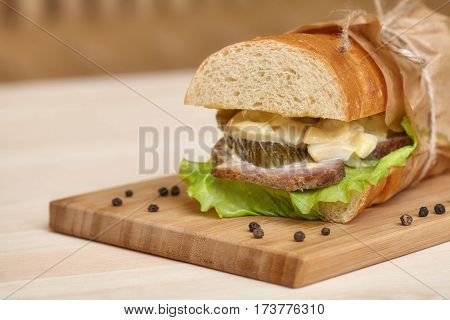 Big sub sandwich baguette with ham and lettuce on wooden cutting board closeup