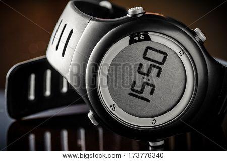 a black digital wristwatch on shiny floor