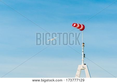 Horizontally flying windsock wind vane with blue sky in the background.