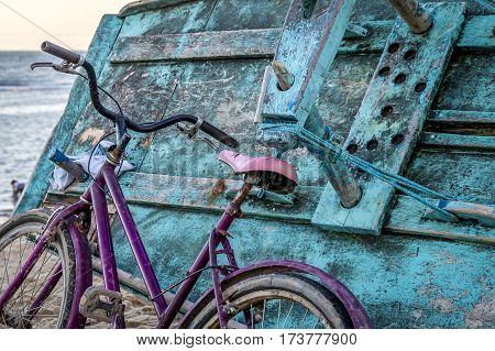 Pink bicycle leaned on turquoise fishermen boat on beach