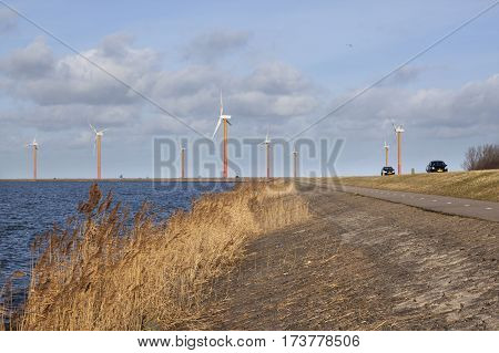 road on the island of flevoland near almere with wind turbines and blue sky with clouds in holland