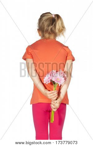 Little girl with flowers behind het back for mother isolated over white background