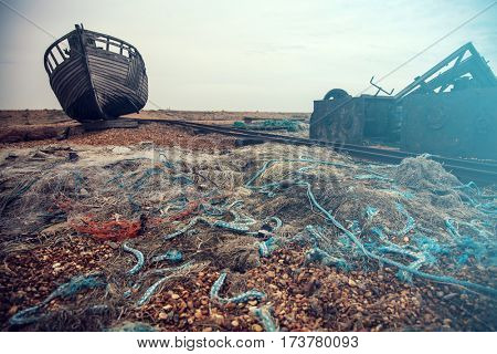 Blue fishing nets and lengths of rope and old boat at Dungeness pebble beach, Kent, England