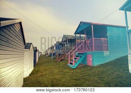 Row of colored beach huts with stormy blue sky on the beach of Tankerton near Whitstable in Kent, UK