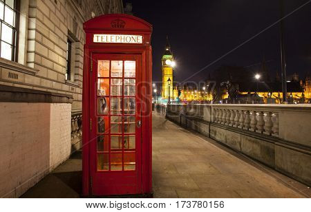Popular tourist Big Ben and Houses of Parliament with red phone booth in night lights illumination