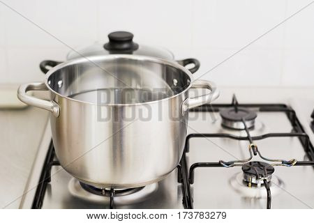 Close-up of stainless steel cooking pot on gas stove in contemporary upscale modern home kitchen. Selective focus on pot.