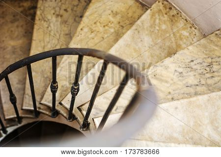 Upside view of indoor spiral winding staircase with black metal ornamental handrail.