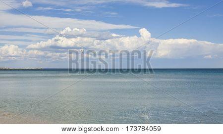 Seascape - blue sea with big white cloud on sky.