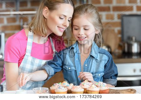 portrait of daughter and mother decorating cupcakes with confetti