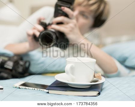 Young female photographer busy with a photo camera a cup of coffee in focus in the foreground