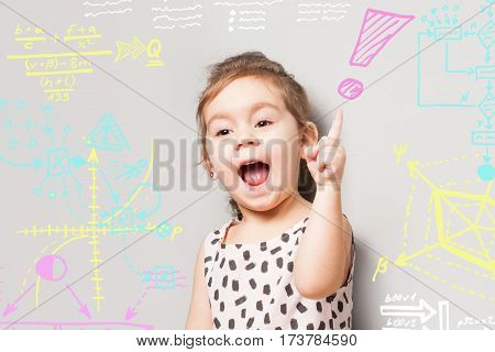 Cute litte girl who looks like found a solution and various quations and diagrams