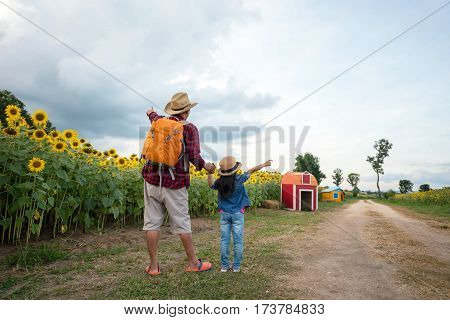The Man And Child Holding Hands At Sunflower Garden.