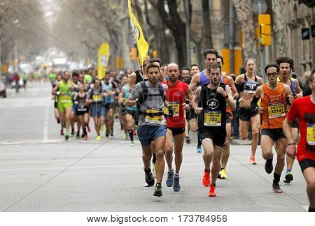 BARCELONA, SPAIN - FEB, 12: Group of runners in through streets running during Barcelona Half Marathon in Barcelona on February 12, 2017 in Barcelona Spain