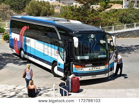 Hersonissos, Greece - July 22, 2016: Two women waiting in Hersonissos on the arrival of the shuttle bus to the airport.