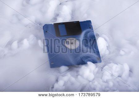 Blue retro floppy disk in clouds. Information cloud. Conceptual. Selective focus