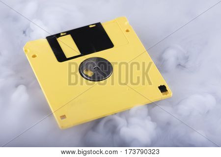Retro floppy disk scratched and yellow. Conceptual photography information cloud. Selective focus