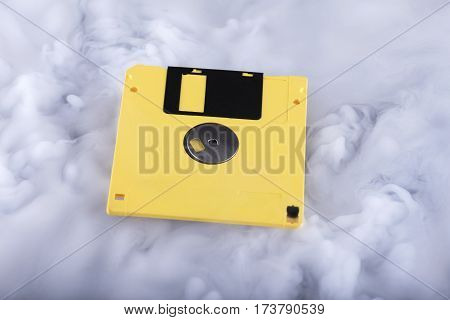 Yellow old and retro floppy disc. Information cloud conceptual image