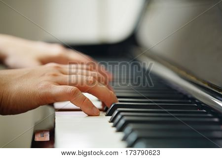 Scene of pianist hands from beside angle with shallow depth of field playing piano. Selective focused.